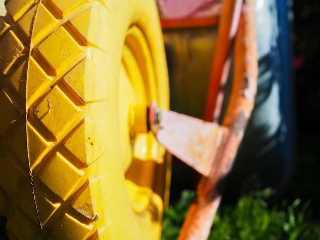 Messa a fuoco selettiva sul battistrada in gomma gialla di un carrello da giardino
