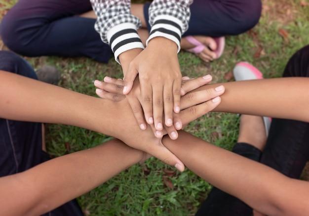 Nel fuoco selettivo delle mani dei bambini piccoli impilate insieme, amicizia, collaboratore, unità, segno di successo e potere, luce sfocata intorno