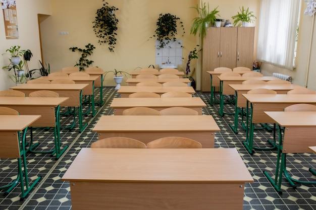 Messa a fuoco selettiva morbida e sfocata. vecchie sedie da conferenza in legno in aula nella scuola povera.