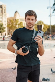 Ragazzo sicuro di sé con fotocamera e smartphone in piedi sulla piazza della città