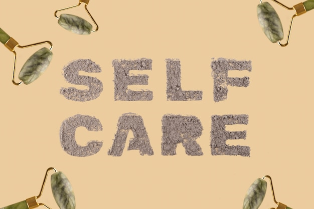 Cura di sé un'iscrizione su uno sfondo beige neutro fatto di argilla naturale per una maschera per la pelle del viso e del corpo tra i rulli massaggianti di giada vista dall'alto laici piatta