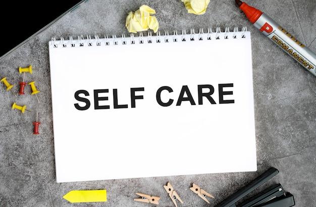 Testo di cura di sé su un taccuino bianco con spilli, pennarello e cucitrice su un tavolo di cemento