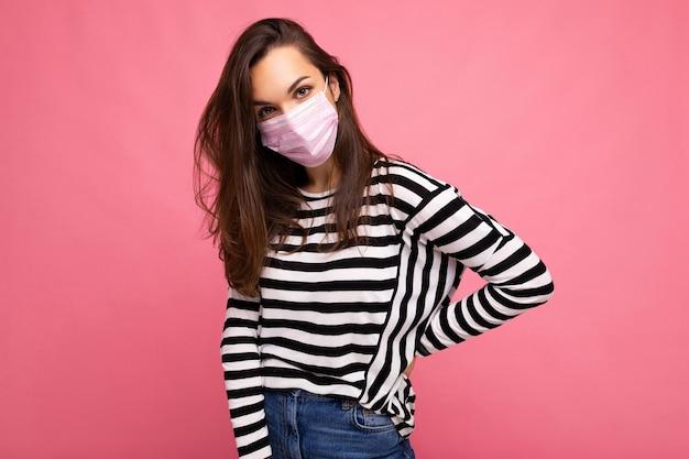 Colpo sicuro di sé di giovane affascinante donna bruna che indossa una maschera facciale mediatica isolata su una parete di fondo rosa.