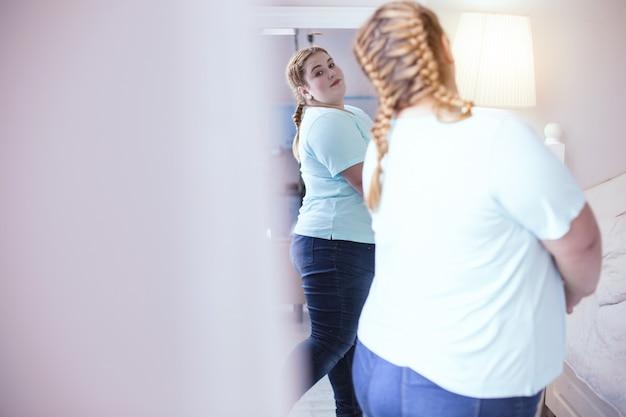 Amore per se stessi. donna dai capelli rossi che gira intorno allo specchio mentre ammira la sua figura