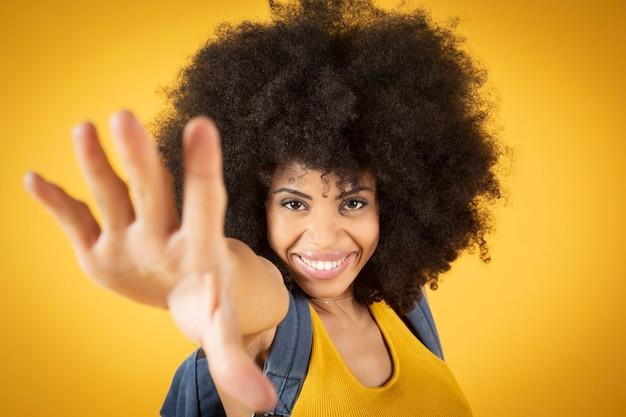 Autoritratto di una giovane e bella donna afro-americana che fa un segno di pace.