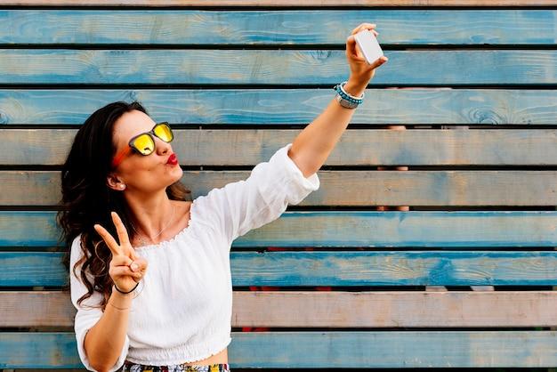 Autoritratto di bella giovane donna che fa il segno di pace. concetto di selfie.