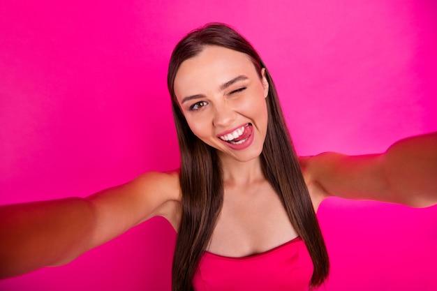 Autoritratto di lei lei bella attraente bella allegra allegra felice ragazza dai capelli lunghi che sbatte le palpebre che mostra la lingua divertendosi isolato su sfondo di colore rosa fucsia vibrante brillante vivido brillantezza