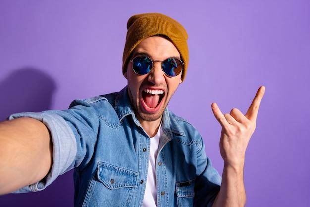 Autoritratto del ragazzo urlante allegro ed elegante alla moda che prende selfie che mostra le dita cornute segno della roccia che indossa il denim marrone del cappuccio isolato sopra fondo di colore vivido viola