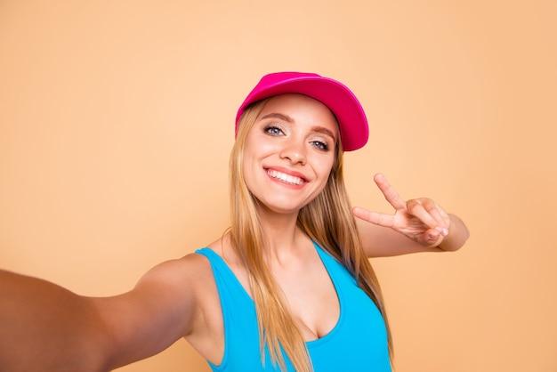 Autoritratto di giovane ragazza sorridente bionda che mostra v-sign