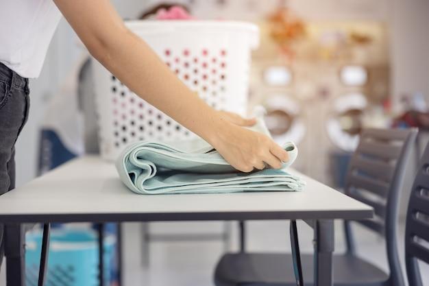 Nella lavanderia self-service con le asciugatrici sullo sfondo, una giovane donna si gode i capi stirati e puliti.