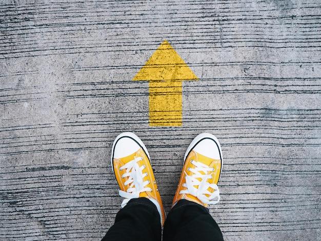 Piedi del selfie che indossano le scarpe da tennis gialle davanti alla freccia sulla strada cementata.