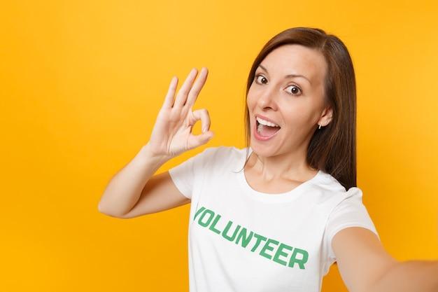Immagine selfie di donna soddisfatta sorridente felice in maglietta bianca con iscrizione scritta volontario titolo verde isolato su sfondo giallo. aiuto volontario di assistenza gratuita, concetto di lavoro di grazia di carità.
