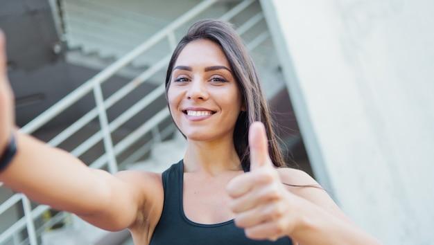 Selfie ritratto di una donna sportiva allegra in abiti sportivi all'aperto in ambiente urbano