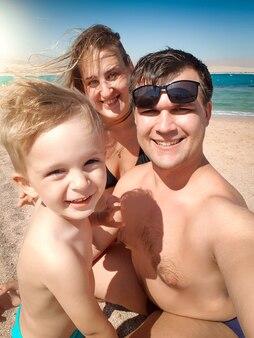 Selfie ritratto di felice sorridente madre, padre e figlio facendo selfie foto sulla spiaggia del mare. famiglia che si rilassa e si diverte durante le vacanze estive.
