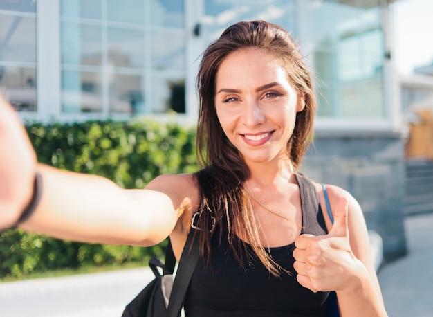Ritratto di selfie giovane donna allegra in forma in top sportivo con borsa sulle spalle sorridendo e mostrando il pollice all'aperto
