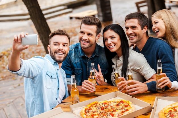 Tempo di selfie! gruppo di giovani allegri che si legano tra loro e si fanno selfie sullo smartphone mentre bevono birra e mangiano pizza insieme
