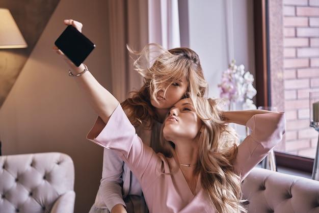 Tempo di selfie! giovani donne giocose in abiti eleganti che si fanno selfie e sorridono mentre sono sedute sul divano