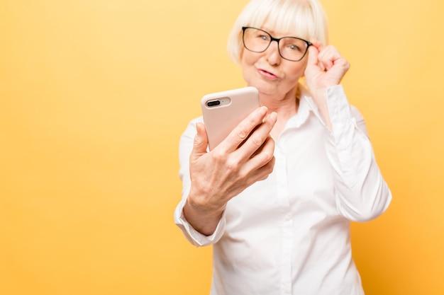 Tempo di selfie! donna invecchiata positiva che sorride mentre usando il telefono isolato sopra priorità bassa gialla.
