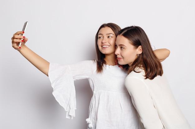 Tempo di selfie, giovane blogger funky sta facendo foto per la sua pagina sui social network. belle amiche che si fanno un'autoscatto con il telefono.