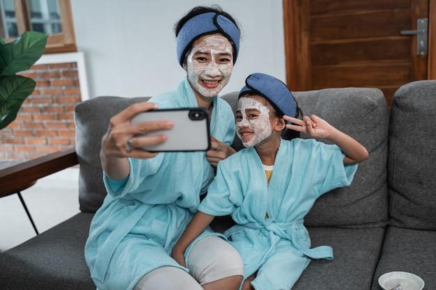 Selfie insieme al telefono cellulare della madre asiatica e della bambina fanno la maschera per la pelle del viso quando ci si rilassa a casa
