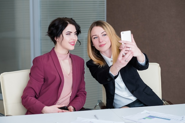 Selfie al lavoro. donne d'affari si divertono alla riunione in ufficio a scattare foto di se stesse.