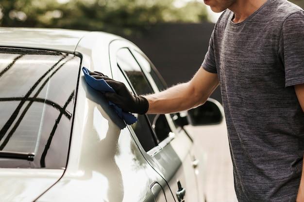 Autolavaggio self-service il giovane pulisce un'auto dopo il lavaggio