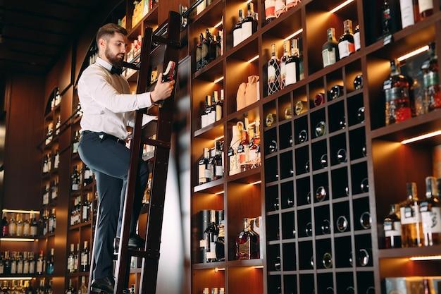 Il venditore di bevande alcoliche ordina le bottiglie in piedi sulla scala