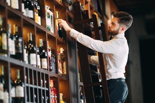 Il venditore di bevande ordina le bottiglie in piedi sulla scala