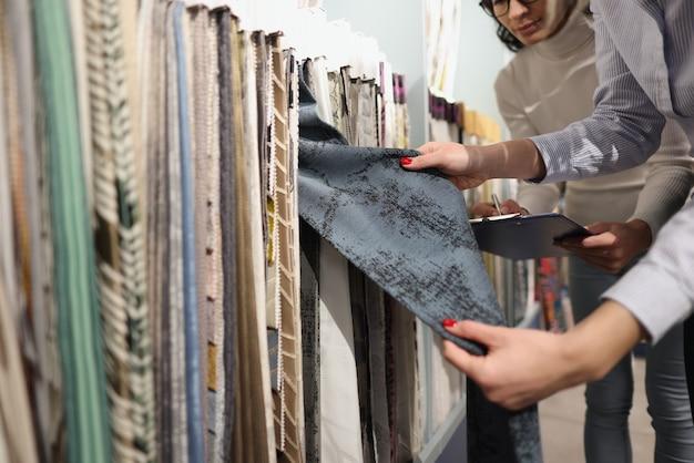 Il venditore e l'acquirente scelgono i tessuti per le tende nella selezione dello showroom dei colori dei tessuti concept
