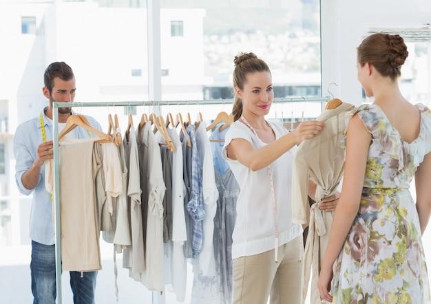 Il venditore che aiuta l'acquirente sceglie i vestiti in negozio