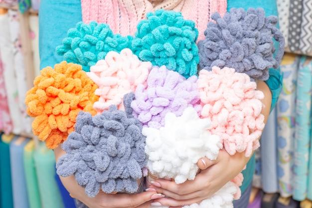 Il venditore tiene tra le mani grovigli di filato color peluche. sullo sfondo del tessuto. un negozio di filati, tessuti e accessori.