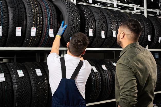 Il venditore offre nuove ruote in gomma, pneumatici, cerchioni per l'auto. cliente maschio è venuto a fare acquisti in un negozio di servizi di auto. meccanico che mostra un assortimento di pneumatici