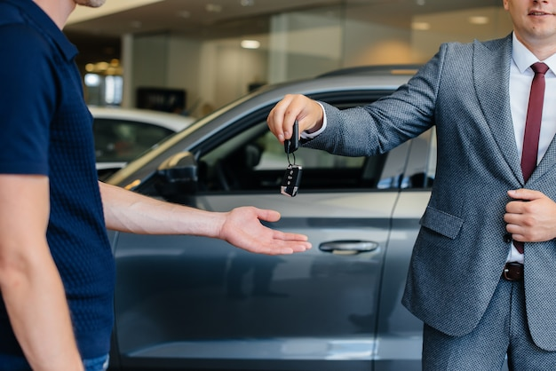 Il venditore passa le chiavi di un'auto nuova a una giovane famiglia