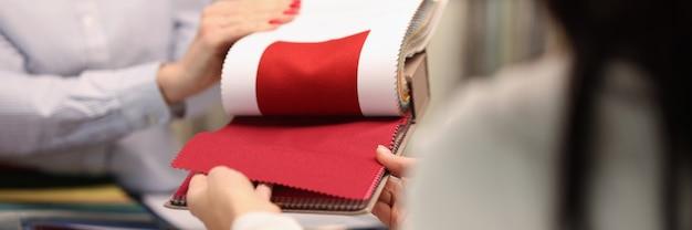 Il venditore mostra al visitatore un tessuto rosso nel concetto di sartoria personalizzata del salone
