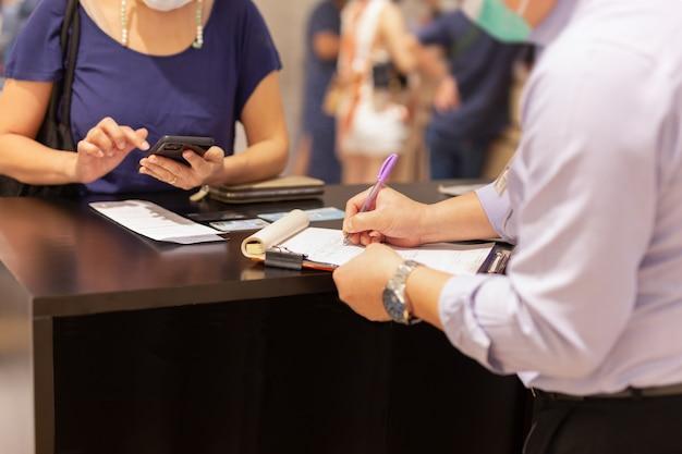 Venditore scrivendo documento contrattuale con cliente donna al bancone del negozio.