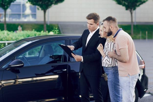 Venditore e una giovane coppia all'aperto vicino a un'auto nuova. il venditore racconta alla giovane coppia della macchina. l'uomo e la donna comprano un'auto.