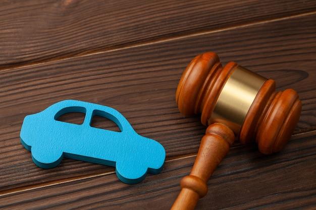 Vendere o acquistare un'auto all'asta. il verdetto su un incidente d'auto, tribunale. macchina blu e martelletto del giudice.