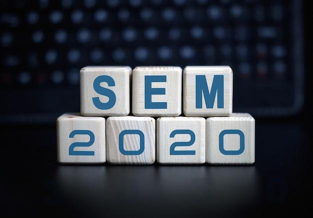 Testo sem 2020 su cubi di legno su uno sfondo monocromatico con riflessione.