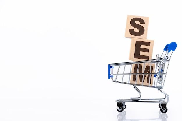 Sem è l'acronimo di search engine marketing. fondo di concetto di affari, sui cubi di legno che si trovano in un carrello della spesa. copia spazio
