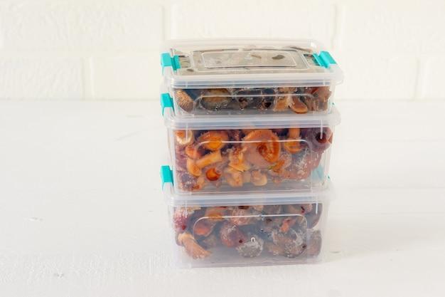 Prodotti semi-finiti. cibo surgelato. agarico di champignon in contenitori di plastica. preparazione del cibo per l'inverno.
