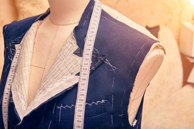 Giacca semipronta su manichino con metro a nastro sul collo. sartoria abito in corso di giacca su misura. sartoria su misura in laboratorio sartoriale. lavorare su una giacca su misura