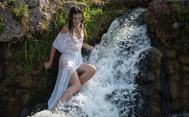 Seminuda giovane donna in abito bianco gode della freschezza e del fresco nei getti d'acqua della cascata