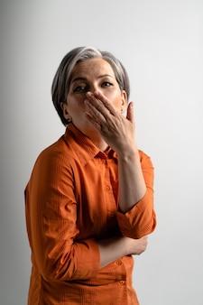L'invio di aria baci donna dai capelli grigi abbastanza matura che indossa camicia arancione sorridente felicemente sul davanti