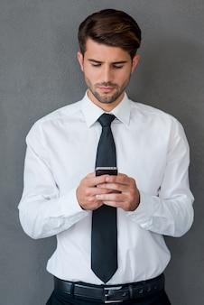 Invio di un messaggio aziendale. bel giovane in camicia e cravatta che buca il telefono cellulare e lo guarda mentre sta in piedi su uno sfondo grigio