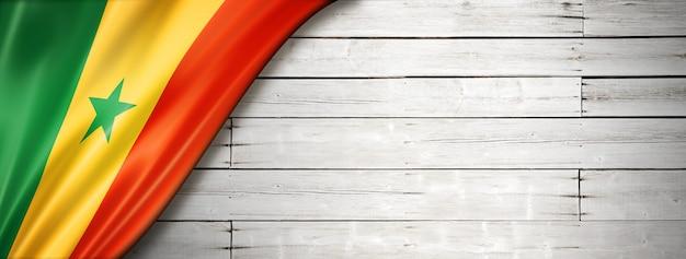 Bandiera del senegal sul vecchio muro bianco. banner panoramico orizzontale.