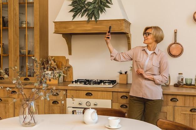 Donna anziana di 50 anni che utilizza app per ordinare l'acquisto di cibo su smartphone seduto in cucina a casa. signora anziana matura che tiene i messaggi di sms del telefono cellulare.