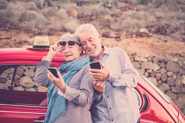 Coppia di adulti anziani controlla e guarda i telefoni cellulari per connettersi a internet o fare un selfie fotografico. auto d'epoca rossa pronta a viaggiare e ovunque sullo sfondo. brama di meraviglia per le persone mature