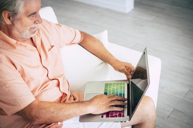 Senior adulto capelli bianchi invecchiato uomo caucasico visto dall'alto utilizzando un laptop colorato per la ricerca sul web