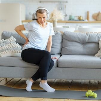 Senior donna adulta che si tocca la schiena sentendo mal di schiena fastidio