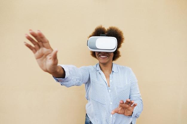 Senior donna africana utilizzando cuffie da realtà virtuale - tendenza tecnologica e gioioso concetto di stile di vita anziano - focus su googles vr